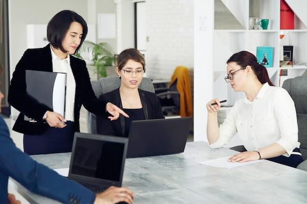 사무실에서 세 명의 성공적인 비즈니스 여성이 프로젝트에서 함께 일하고 있습니다.