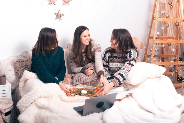 3人の若い女性が寒い日にピザと一緒に女の子の夜を過ごしています。
