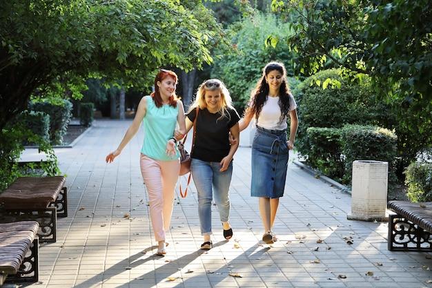 3人の若い女性の友人が公園の路地を歩いています