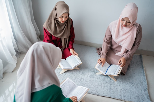 Three young women wearing hijabs read the holy book of the al-quran together