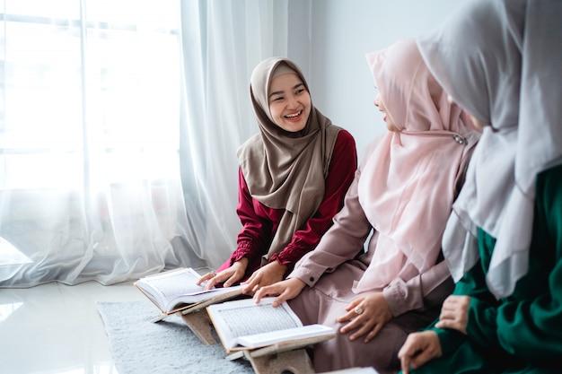 Три молодые женщины в хиджабах вместе читают священную книгу аль-корана