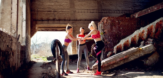 Three young women wearing sports outfits while holding hands together before starting workout outdoors.