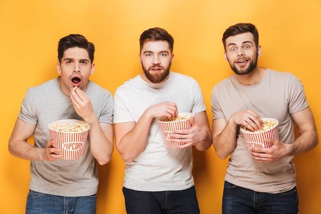 ポップコーンを食べて心配している3人の若い男性