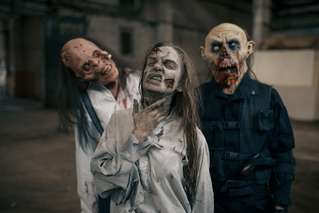 Three zombies in abandoned factory, scary place. horror in city, creepy crawlies attack, doomsday apocalypse, bloody evil monsters