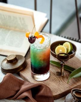 Трехцветный холодный коктейль на столе