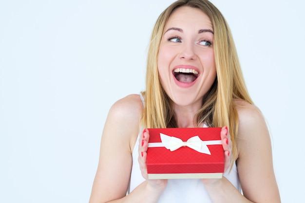 선물 상자와 함께 흥분하고 흥분된 여성. 생일이나 여성의 날에 깜짝 선물.