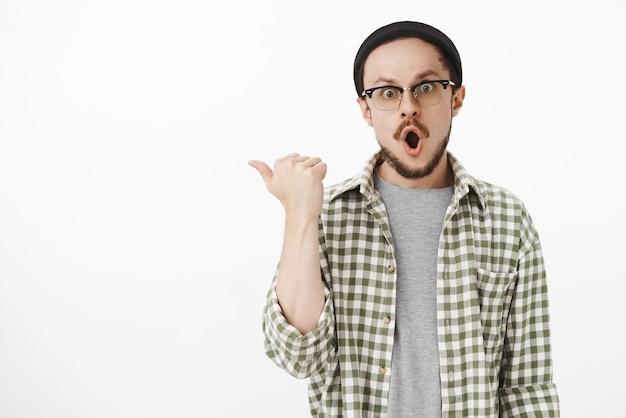 Взволнованный и впечатленный молодой хипстерский парень с бородой в клетчатой зеленой рубашке, указывая пальцем влево, говорит: «вау», скривив губы, высовывая глаза от изумления над серой стеной