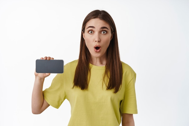 Thrilled girl shows horizontal smartphone screen, gasp and say wow, showing application on mobile phone, interface of app on cellphone, standing on white.