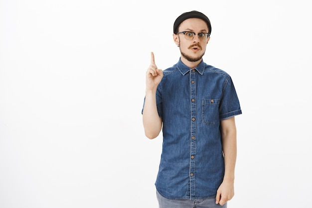Thrilled good-looking smart european male coworker in glasses and trendy black beanie raising index finger in eureka gesture folding lips and gazing adding suggestion