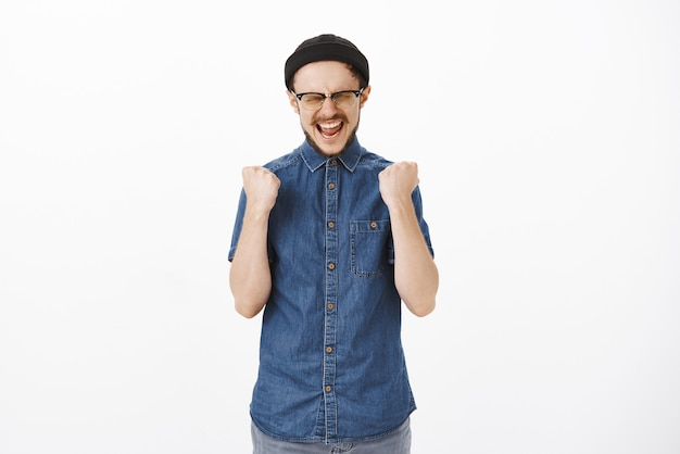 Thrilled happy and delighted good-looking young male in beanie and glasses yelling yes raising clenched fists near chest in victory or success gesture celebrating, triumphing win