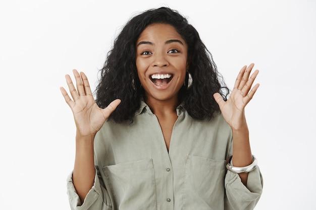 유행 복장에 곱슬 헤어 스타일을 가진 감동적인 수다쟁이 행복 아프리카 계 미국인 여자는 즐겁게 몸짓으로 손바닥을 높이고 기쁘게 미소 짓습니다.