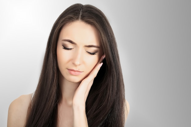 Throat pain. beautiful woman having sore throat, feeling sick. unhappy ill female suffering from painful swallowing, strong pain in throat, holding hand on her neck. health concept.