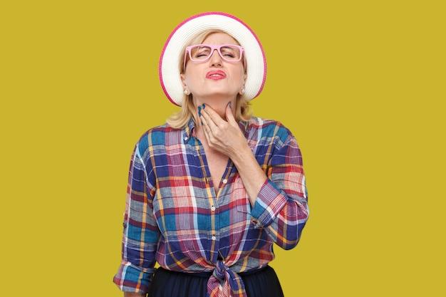 인후통 또는 독감. 모자와 안경을 쓰고 고통스러운 목을 잡고 있는 캐주얼한 스타일의 아픈 현대적인 성숙한 여성의 초상화. 노란색 배경에 고립 된 실내 스튜디오 촬영