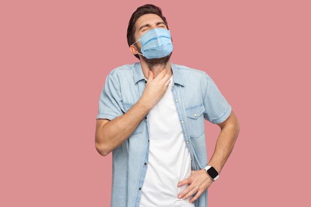 인후통이나 감기 독감. 파란 셔츠에 외과용 마스크를 쓴 슬픈 젊은 남자의 초상화가 고통스러운 목을 잡고 비명을 지르고 있습니다. 분홍색 배경에 고립 된 실내 스튜디오 촬영