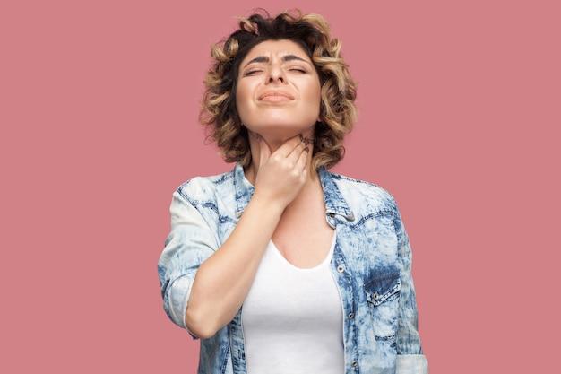 목이 아프거나 감기. 파란 셔츠에 곱슬머리를 한 젊은 여성의 초상화가 서 있고 아픈 목을 안고 있습니다. 실내 스튜디오 촬영, 분홍색 배경에 격리.