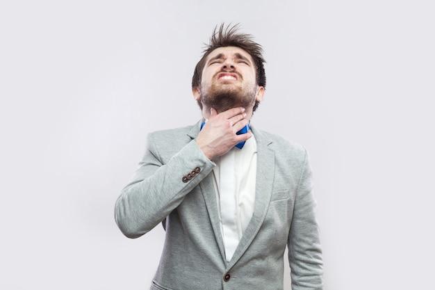 목 통증. 회색 양복에 파란색 나비 넥타이를 매고 서서 고통스러운 목을 잡고 있는 수염난 잘생긴 남자의 초상화. 밝은 회색 배경에 격리된 실내 스튜디오 촬영.