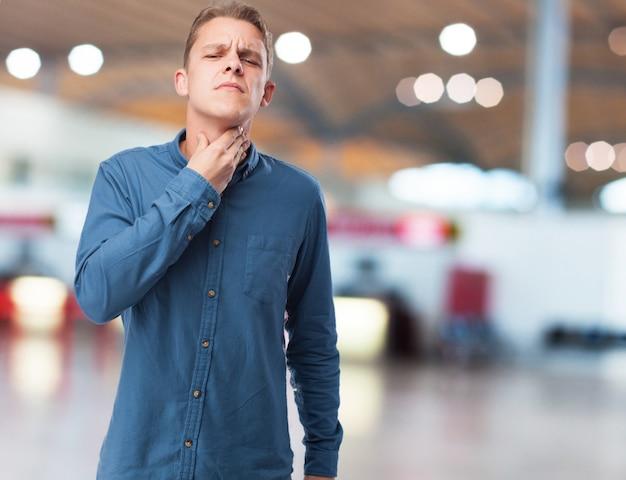Сердитый молодой человек страдает throatache