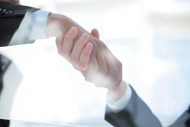 Through the glass.business background. handshake of business partners above the desk