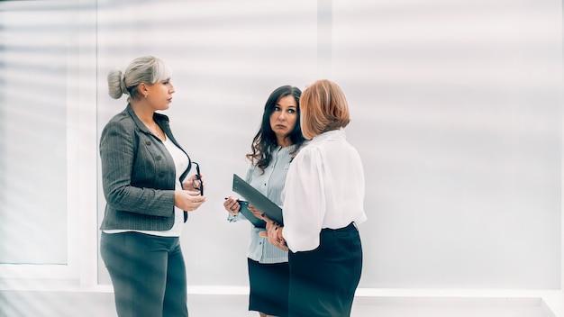 Через жалюзи группа деловых женщин разговаривает в холле офиса.