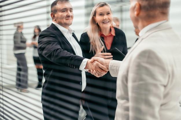 Через шторы предприниматель встречает своего делового партнера