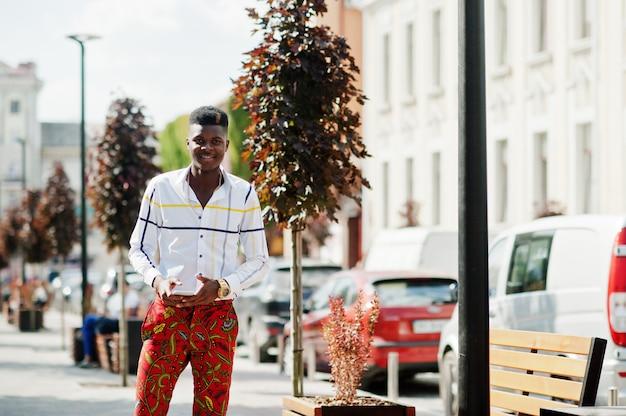 Портрет красивого стильного афро-американского модельного человека в красных throusers и белой рубашке с сотовым телефоном под рукой.