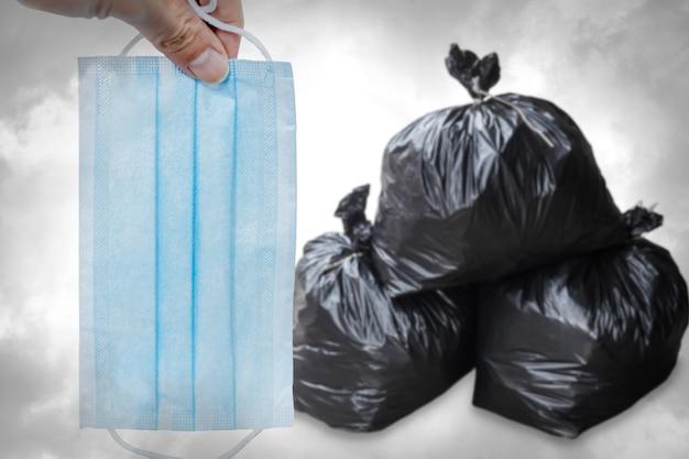使用済みの使い捨てフェイスマスクや感染したフェイスシールドをゴミ箱に捨てる、感染性ゴミ廃棄物の危険性の概念。