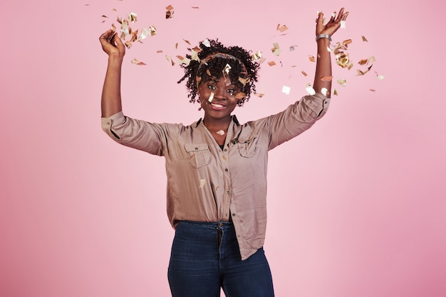 Бросать конфетти в воздух. афро-американская женщина с розовой предпосылкой позади