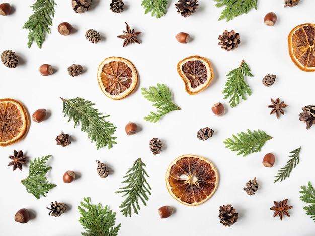 フラットは、植物やスパイスの部分の創造的な自然な背景を置きます。 thuja、コーン、乾燥オレンジスライス、白い背景の上のスパイス。上面図