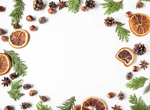 フラットは、植物、ナッツ、スパイスの部品の創造的な自然なフレームを置きます。 thuja、コーン、乾燥オレンジスライス、白い背景の上のスパイス。トップビュー、コピースペース