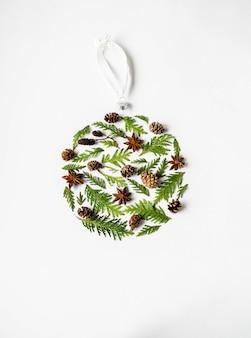 フラットは、白い背景の植物部分の創造的な自然なレイアウトクリスマスボールを置きます。 thuja、コーン、植物の植物概念セット。コピースペース、トップビュー