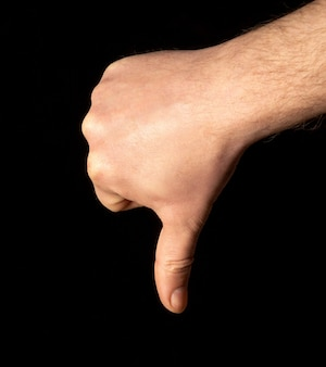 Thumb down male hand sign isolated on black background