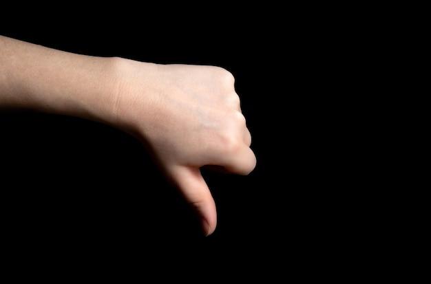 暗い黒の背景に親指ダウンサイン手のジェスチャー