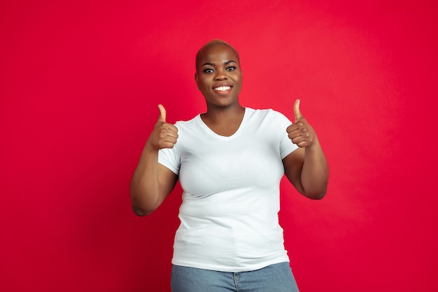 Thumb up. african-american young woman's portrait on red. beautiful female model in shirt.