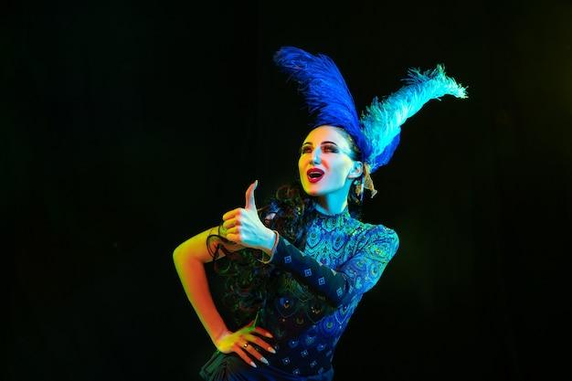 いいね。カーニバルの美しい若い女性、ネオンの光の中で黒い壁に羽を持つスタイリッシュな仮面舞踏会の衣装。広告のコピースペース。休日のお祝い、ダンス、ファッション。お祝いの時間、パーティー。