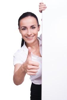 Палец вверх. красивая молодая женщина, стоящая рядом с копией пространства и улыбаясь, пока изолирована на белом