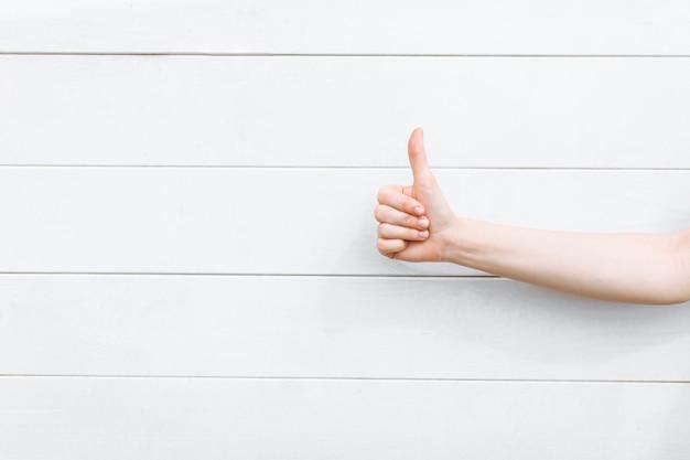 白い木製の壁にクローズアップを親指します。