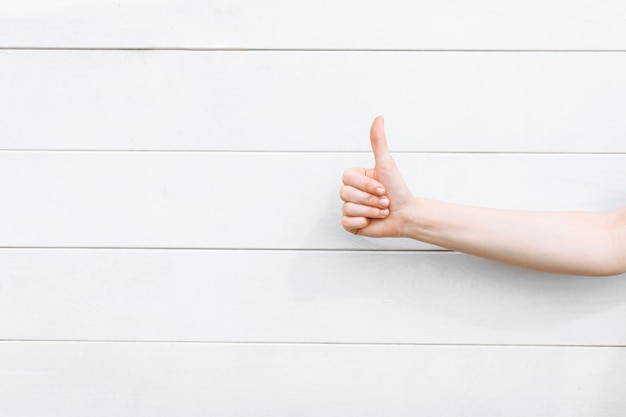 Thumb up close-up on white wooden wall