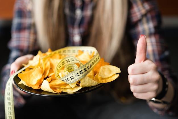 건강에 좋은 음식을 위해 엄지 손가락. 다이어트 영양과 균형 잡힌 식사. 슬림하고 핏감있는 몸매와 체중 감량을위한 홈 메이드 구운 칩