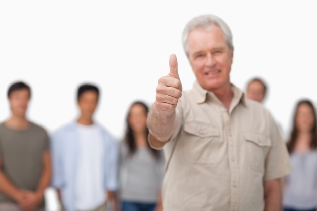 Thumb up given by mature man with young people behind him
