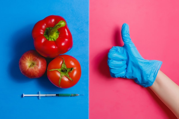 Thumb up green liquid in syringe, red tomato, apple, pepper. genetically modified food concept on pink blue.