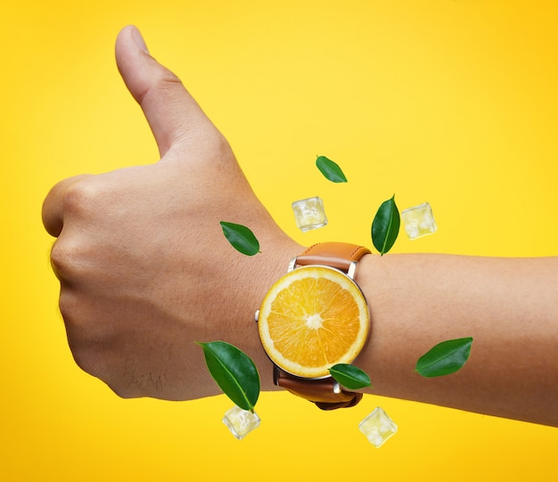 Thumb up hand wearing fruit orange watch green leaves and ice cube flying around
