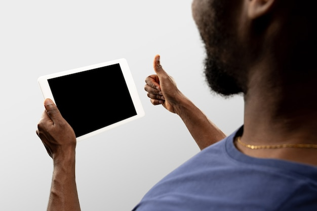 Thumb up, like. close up male hands holding smartphone with blank screen during online watching of popular sport matches, championships. copyspace for ad. devices, gadgets, technologies concept.
