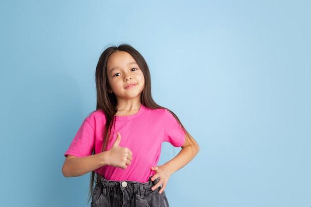 Pollice in su, bel gesto. ritratto della bambina caucasica sulla parete blu. bellissimo modello femminile in camicia rosa.