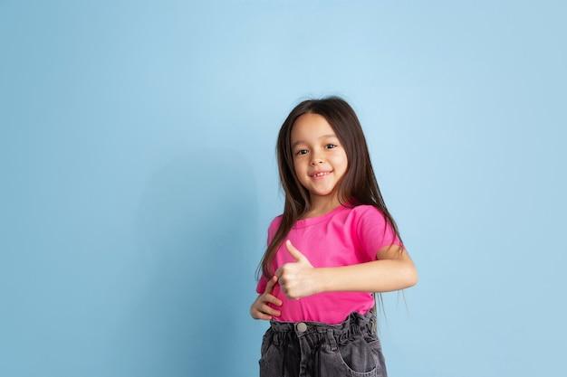 親指を立てて、いいジェスチャー。青い壁に白人の少女の肖像画。ピンクのシャツの美しい女性モデル。人間の感情、顔の表情、若者、子供時代の概念。
