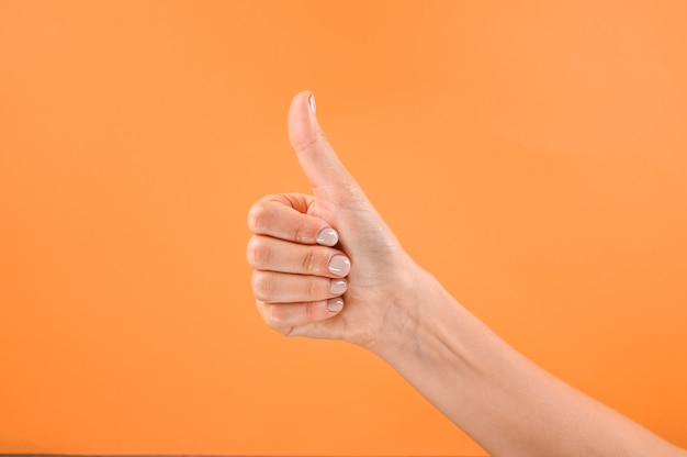 오렌지 배경에 엄지 손가락.