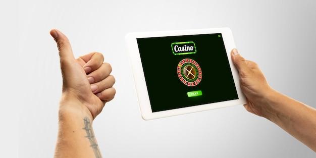 Палец вверх. азартные игры онлайн, концепция казино. рука, держащая устройство с лотереей, крышка казино, изолированные на белом фоне. покер, букмекерство, азартные игры, современные технологии, бизнес и финансы. copyspace.