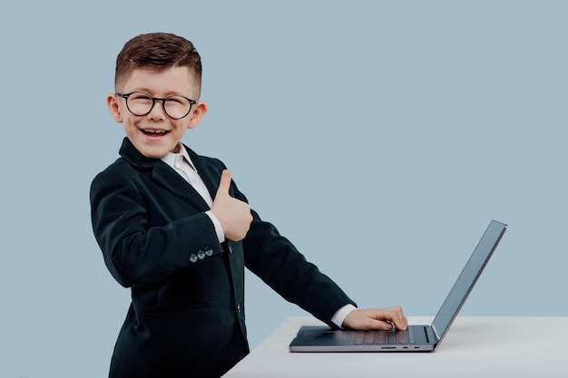 Thumb up positive schoolboy in suit and glasses smiling and looking at camera while standing near ta...