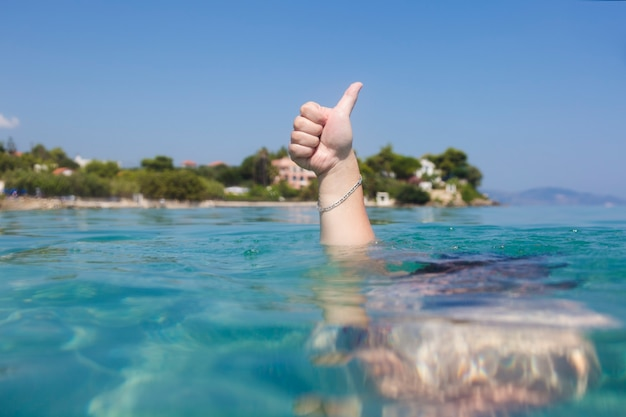 ギリシャ、ザキントス島のイオニア海の水中からの親指を立てるサイン。成功した夏の休日の概念