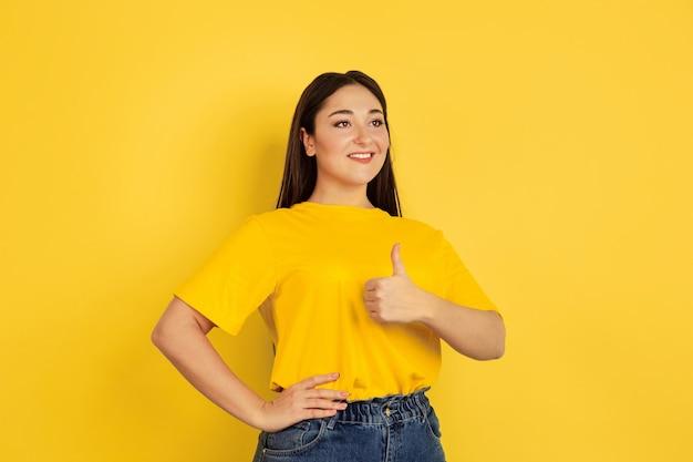 親指を立てて、笑顔。黄色の壁に分離された白人女性の肖像画。カジュアルなスタイルの美しい女性のブルネットモデル。人間の感情、顔の表情、販売、コピースペースの概念。