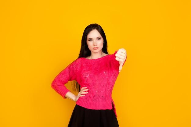 親指を下にして、明るい白い壁に女性を示しています。不承認と低品質、評価が低く、結果が悪いという概念。